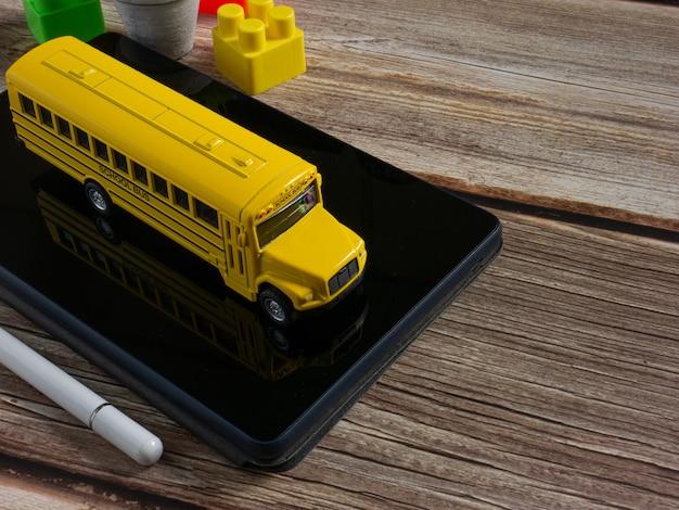 Le bus scolaire sur tablette pour l'éducation ou le concept d'apprentissage en ligne