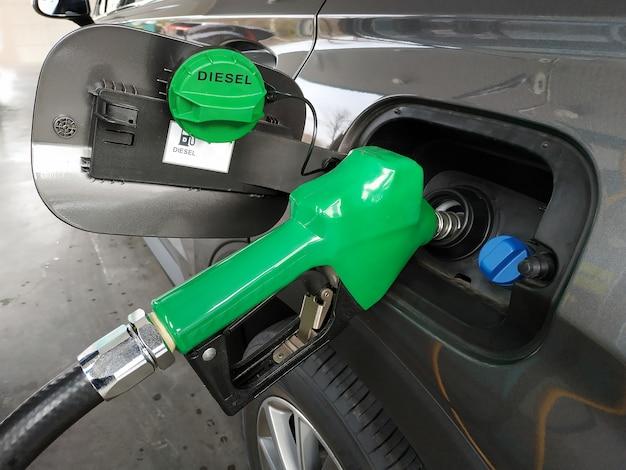 Buses à carburant ajoutant du carburant diesel dans une voiture à une station d'essence à pompe.