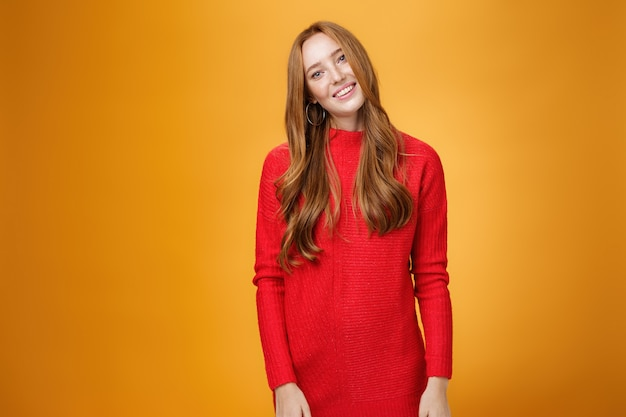 Busiensswoman élégante et attrayante aux cheveux roux en robe tricotée rouge inclinant la tête et souriante séduisante et posant joyeusement sur fond orange en écoutant avec intérêt la conversation