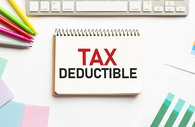 Businesman tenir le bloc-notes avec texte franchise d'impôt fond blanc business