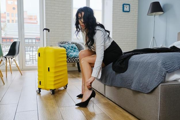 Business belle femme assise sur le lit à l'hôtel, fatiguée après un voyage d'affaires femme décollant les chaussures