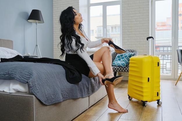 Business belle femme assise sur le lit à l'hôtel, fatiguée après un voyage d'affaires