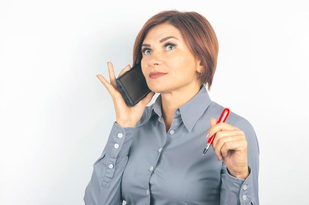 Business belle femme parle au téléphone avec un stylo à la main