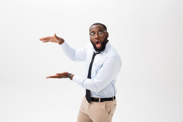 Business concept - afro-américain étonné, tenant les deux mains sur le côté, présentant des projets sur fond gris.