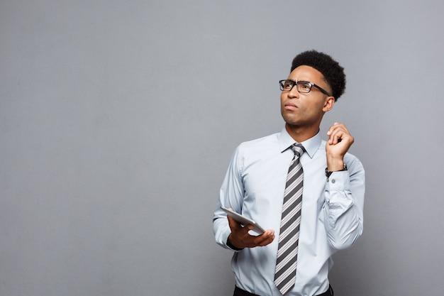 Business concept - heureux bel homme d'affaires afro-américain professionnel choquer et penser avec tablette numérique sur sa main.