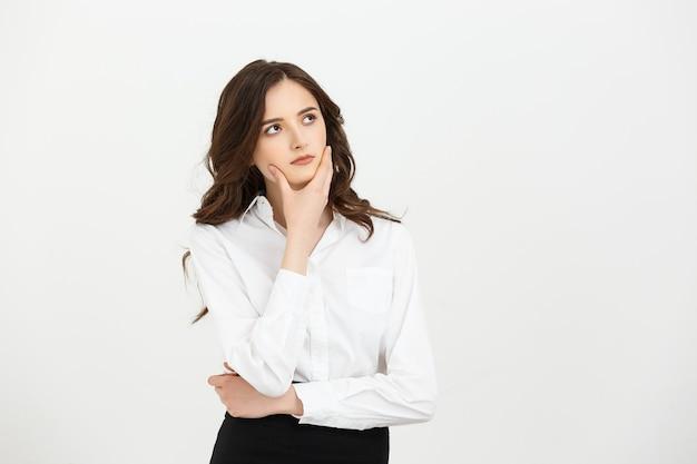Business concept réfléchie femme d'affaires avec un doigt sous le menton à la recherche d'isoler