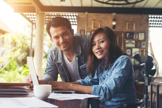 Business couple fonctionne avec un ordinateur portable ensemble à café.