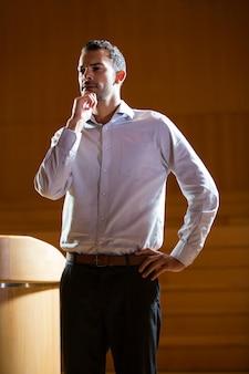 Business executive faisant des gestes tout en prononçant un discours au centre de conférence