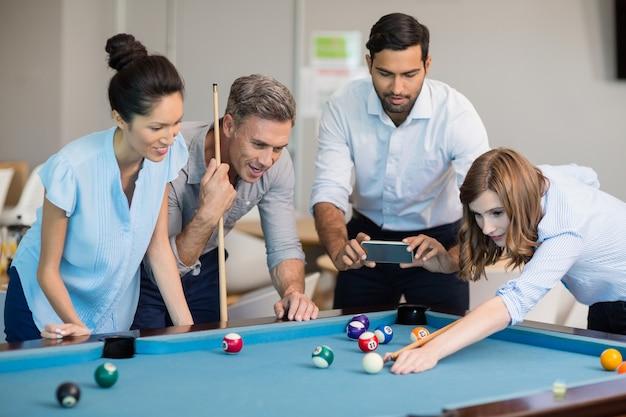 Business executive prenant une photo avec un téléphone mobile pendant que des collègues jouent au billard