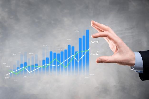 Business man holding montrant des graphiques holographiques et des statistiques boursières gagner des bénéfices.