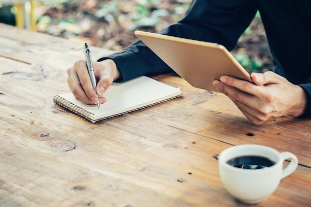Business man main bloc-notes écriture de main et la tablette de maintien dans le café avec filtre vintage.