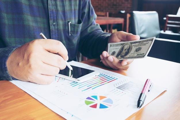 Business man sms sur téléphone portable et holding dollar bank note dans la main