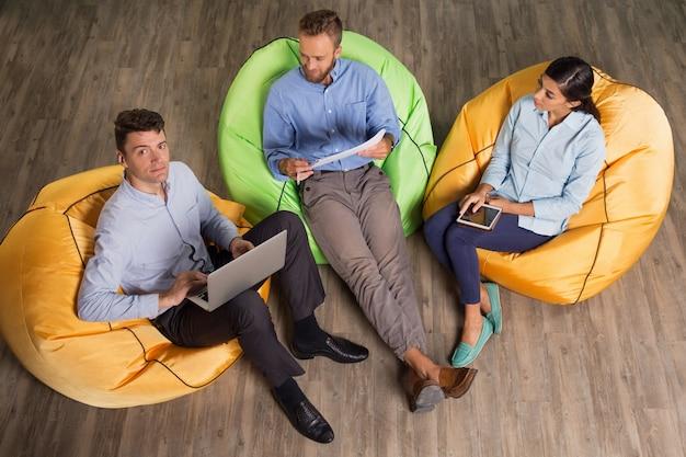 Business team travaillant sur le projet sur les chaises beanbag