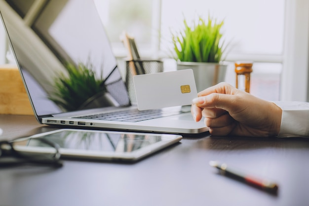 Business woman utilise la carte de crédit pour magasiner en ligne avec un ordinateur portable et une tablette