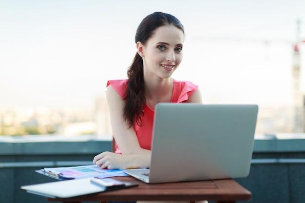 Businesslady attrayant en chemisier rose s'asseoir sur le toit et travailler avec un ordinateur portable