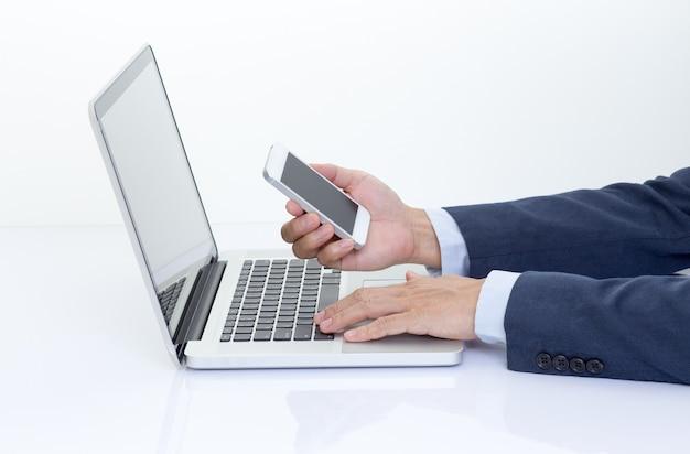 Businessman hand holding mobile phone avec ordinateur portable