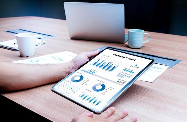 Businessman hand holding tablet avec présentation du diaporama du rapport financier sur l'affichage