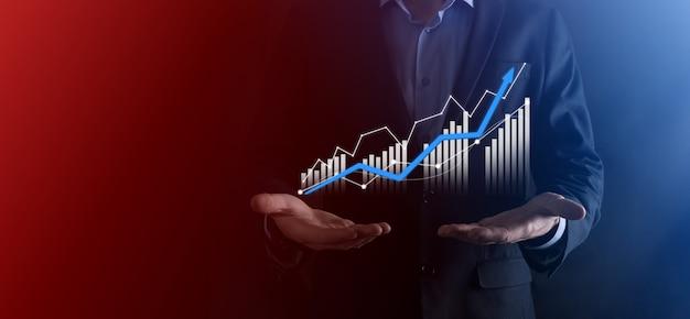 Businessman hold dessin sur écran graphique croissant, flèche de l'icône de croissance positive.