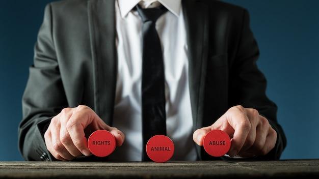 Businessman holding cercles de coupe en bois rouge avec droit des animaux et signe de maltraitance des animaux dans une image conceptuelle