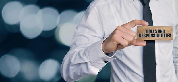 Businessman holding 'rôles et responsabilités' texte sur découpe en bois