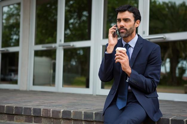Businessman holding tasse de café jetable parler sur téléphone mobile dans le centre de conférence