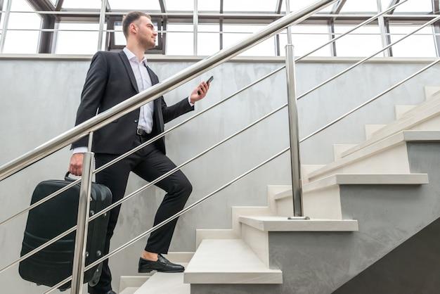 Businessman holding valise en cours d'exécution dans les escaliers dans un bâtiment moderne