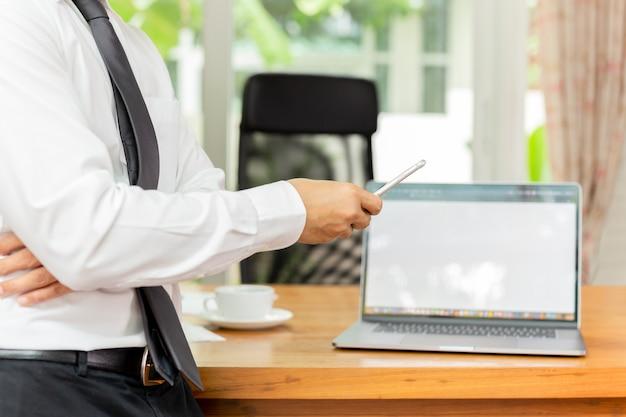 Businessmans main tenant un téléphone portable avec ordinateur portable sur un bureau en bois