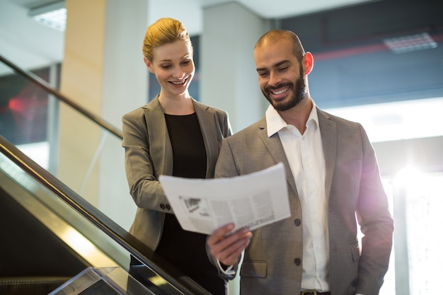 Businesspeople standing on escalator avec bagages