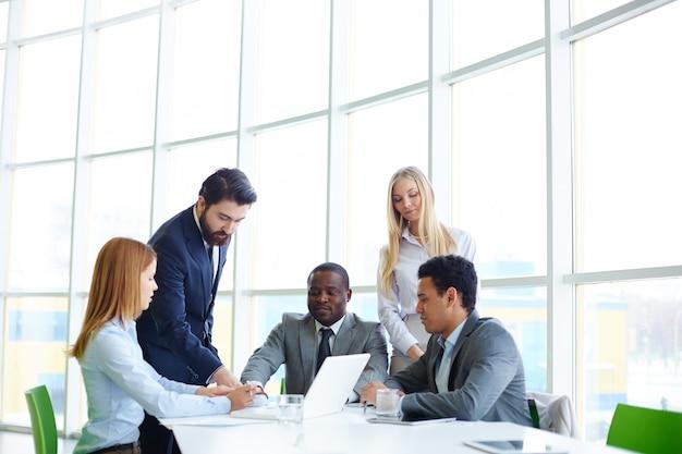 Businesspeople travaillant en équipe avec un ordinateur portable