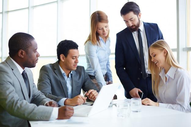 Businesspeople travaillant sur ordinateur portable dans le bureau