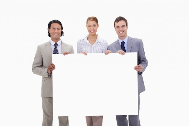 Businessteam tenant une pancarte blanche