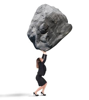 Businesswoman brandissant un gros rocher lourd