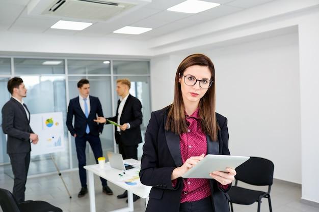 Businesswoman brunette dans des verres sur les gens d'affaires de fond un bureau