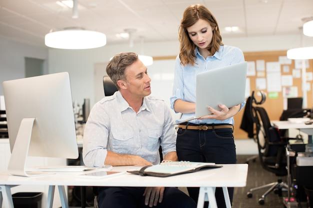 Businesswoman discuter avec un collègue masculin tout en travaillant au bureau