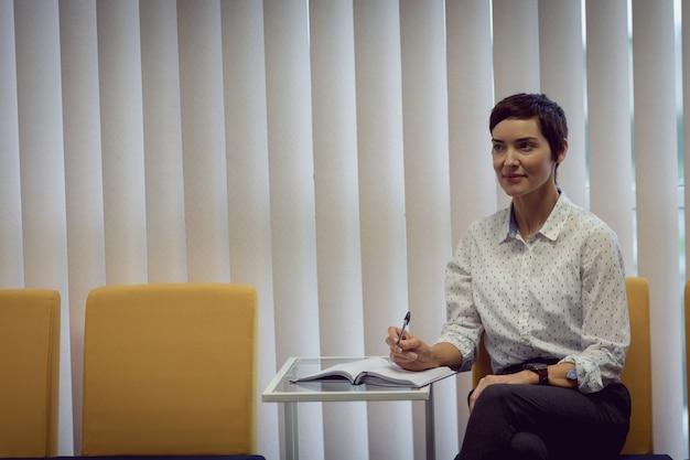Businesswoman écrit sur le journal au bureau