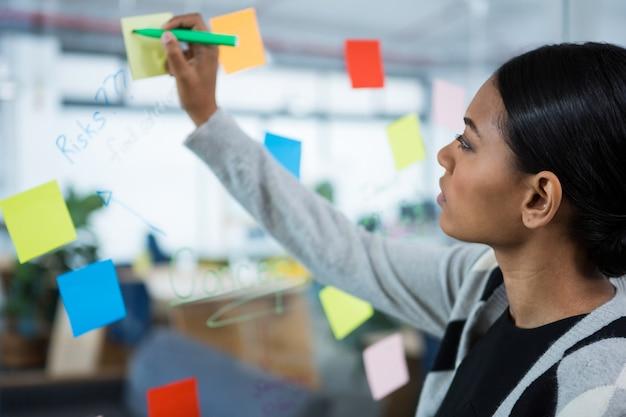 Businesswoman écrit sur pense-bête