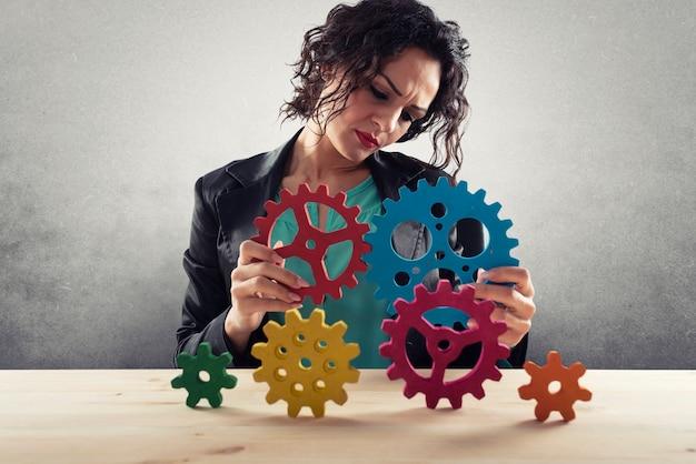 Businesswoman essaie de connecter les pièces d'engrenages concept de partenariat et d'intégration de travail d'équipe