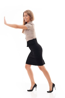 Businesswoman essayant de pousser quelque chose
