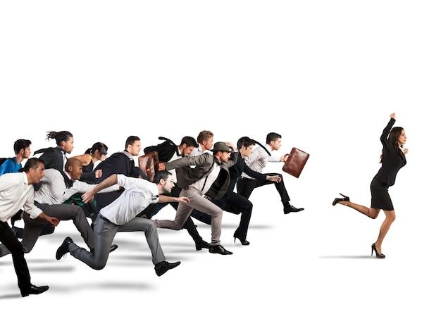 Businesswoman exulte de gagner lors d'une course avec des adversaires