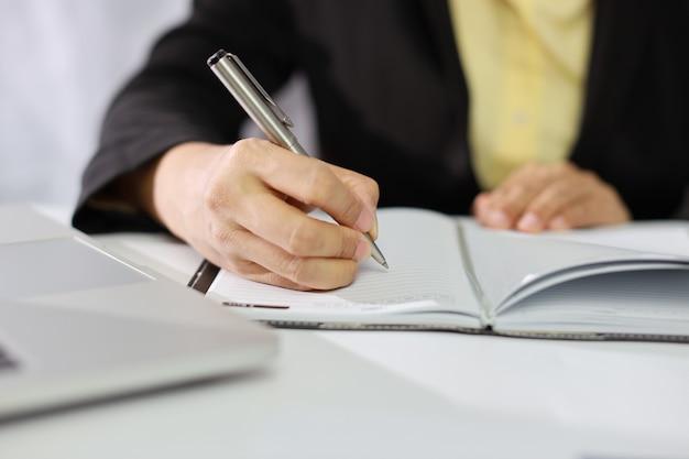 Businesswoman hands in black suit sitting and writing notebook et travaillant ou utilisant un ordinateur sur un tableau blanc avec du travail sur papier