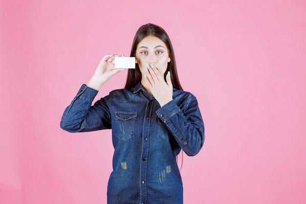 Businesswoman holding carte de visite et couvrant sa bouche