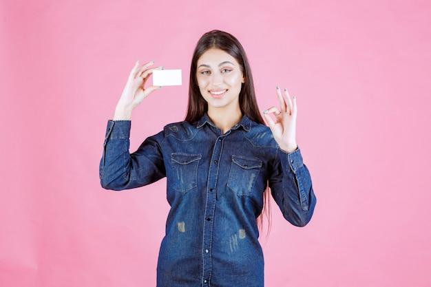 Businesswoman holding carte de visite et montrant le signe de la main de plaisir