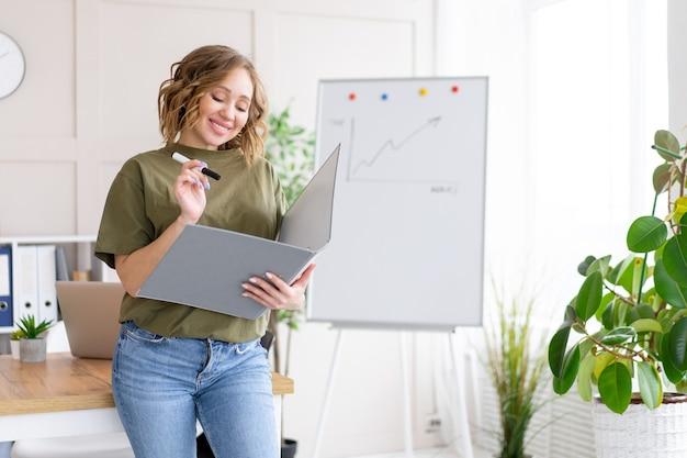 Businesswoman holding dossier pour marqueur d'écriture papier