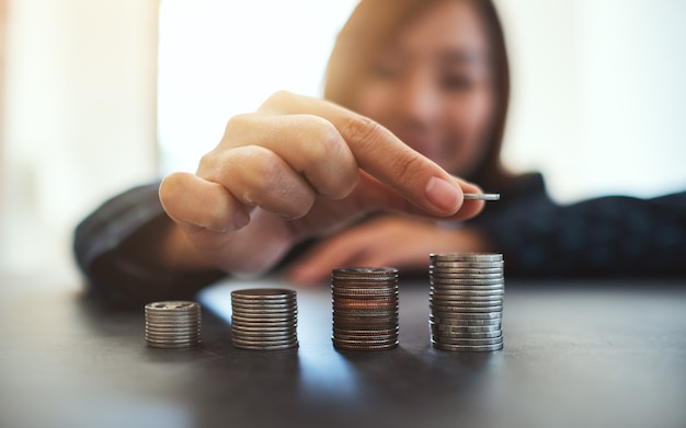 Businesswoman holding et empiler des pièces sur la table