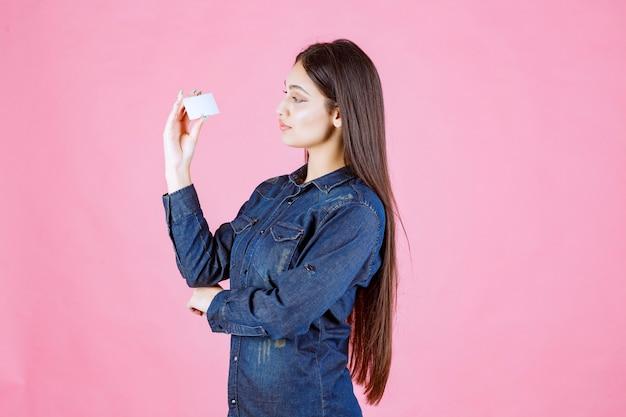 Businesswoman holding et en regardant sa carte de visite