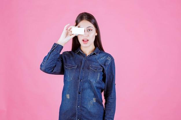Businesswoman holding sa carte de visite à ses yeux