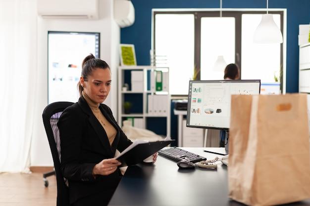 Businesswoman in corporate start up office analysant des documents, graphique en regardant le presse-papiers