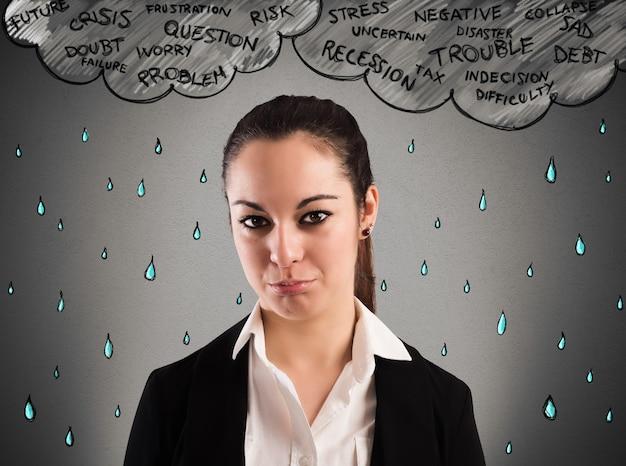 Businesswoman pleurer avec un nuage au-dessus de sa tête et de la pluie