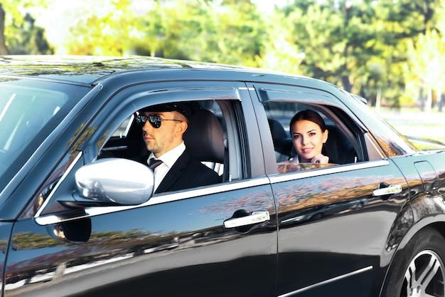 Businesswoman riding une voiture avec chauffeur