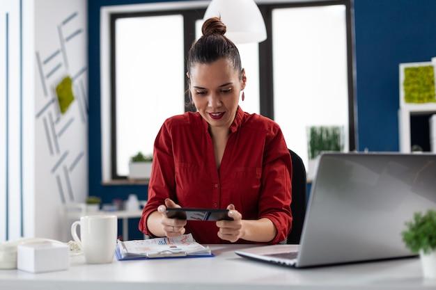 Businesswoman sitting at desk in corporate office jouer à des jeux vidéo à l'aide de smartphone entrepreneur t...